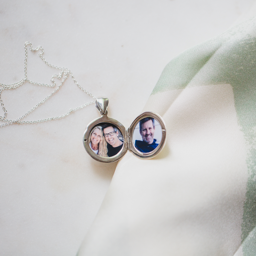 Round silver locket with two photos inside, one of couple embracing and smiling at camera and the other of just the man