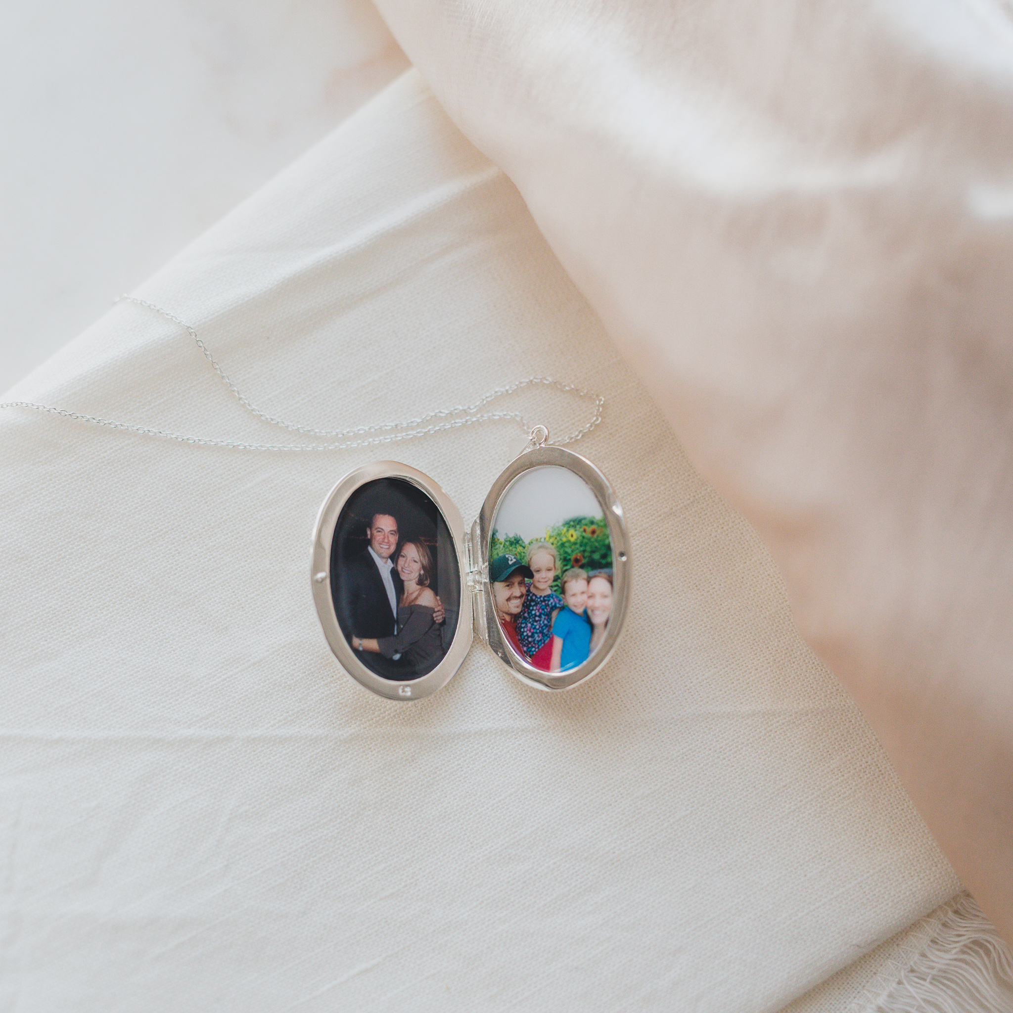 pictures of a family of four together, and a couple together, inside a large silver etched photo locket